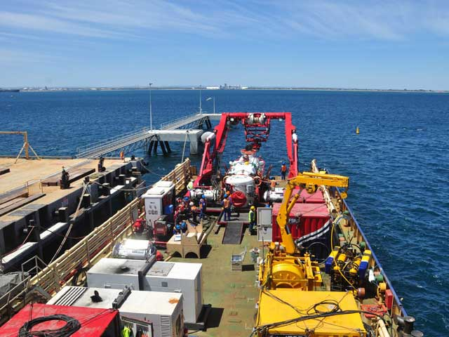 Seated on the deck is the scorpio 45 remote operated vessel with winch 7a, the universal deck reception chamber, one man transfer chamber, the portable handling systems A-frame, the LR5 Submarine Rescue Vessel, containers, workshop, cradles, and herons.