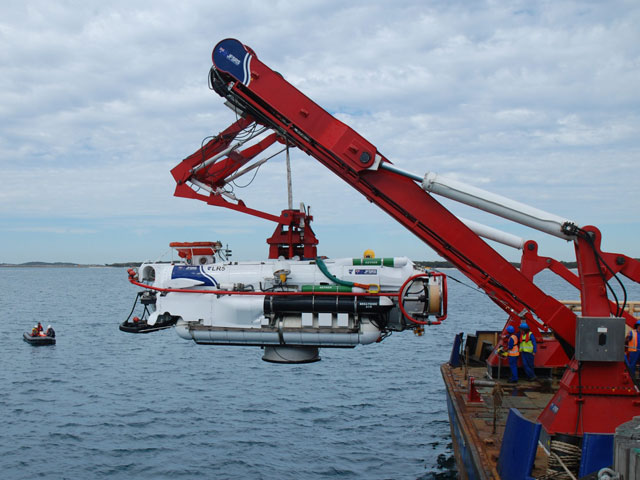 Portable handling systems work boat swimmers watch as the LR5 Submarine Rescue Vessel is lowered in to the water via the launch and recovery A-frame on the rear deck of Trials and Safety Vessel Seahorse Standard.
