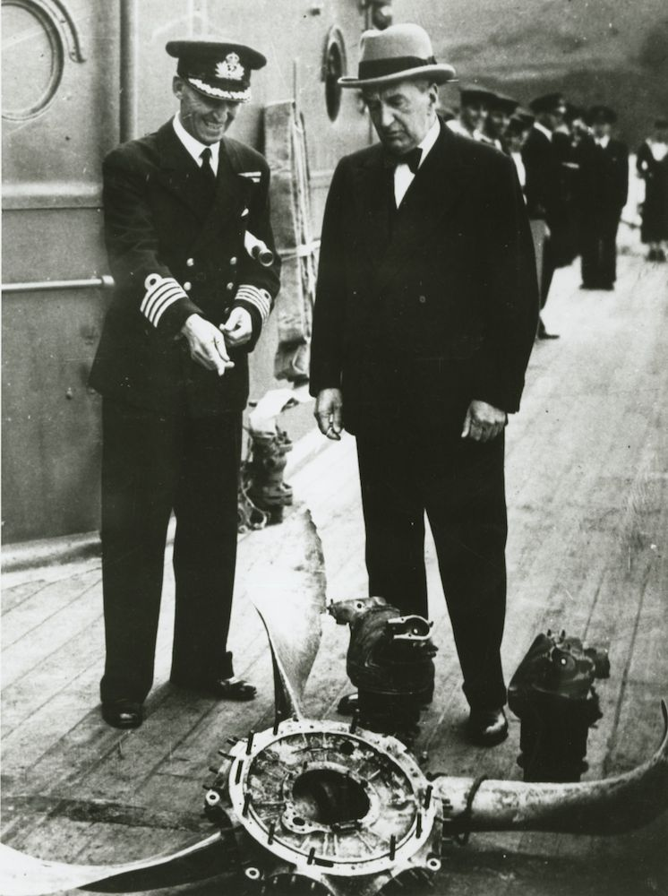 Captain J.M. Armstrong, RAN in conversation with Mr S.M. Bruce, the Australian High Commissioner to England, in July 1945 following the ships arrival at Plymouth. Visible in the foreground is the propeller of one of the Japanese kamikaze aircraft that struck Australia during the bitter fighting in the seas surrounding the Philippines. (AWM 107002)