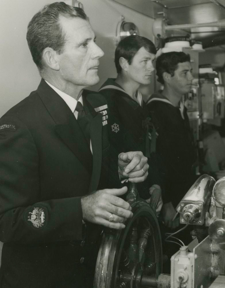Warrant Officer Tim Collins, OAM, a well known RAN personality at the helm of Stalwart in 1983. With him are Leading Coxswain L. Westbrook and Able Seaman Quarter Master Gunner P. Gearing