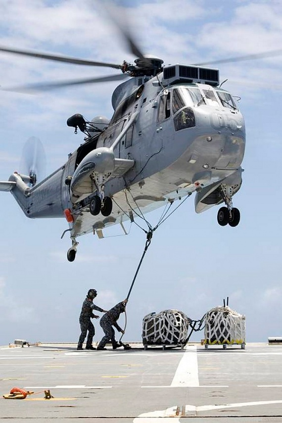A Mk50A Sea King helicopter of 817 Squadron lifts a palletised load of musical instruments, belonging to the sea deployment group of the Royal Australian Navy Band, for transfer from HMAS Kanimbla to the USS Cleveland. The Band are cross decking to USS Cleveland and USS Bon Homme Richard to provide entertainment to US Marines and sailors, and Australian Regular Army soldiers embarked on the two ships.