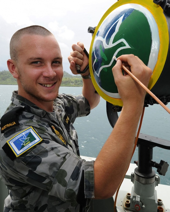 Seaman Nicolas Love paints the back of the ten inch light with the RAMSI logo during HMAS Brunei's deployment in the Solomon Islands in 2010