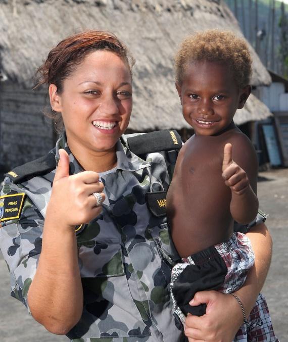 Seaman Writer Kim-Jade Martin from HMAS Tobruk meets a Papua New Guinean boy at a small coastal villiage in Rabaul during PACIFIC PARTNERSHIP 2010.