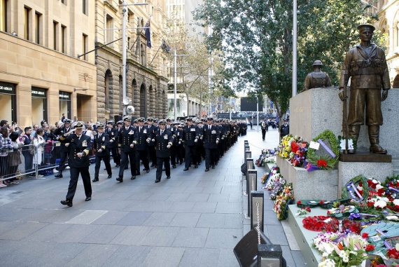 Navy officers and sailors from HMAS Watson march past the Martin Place Cenotaph in Sydney.