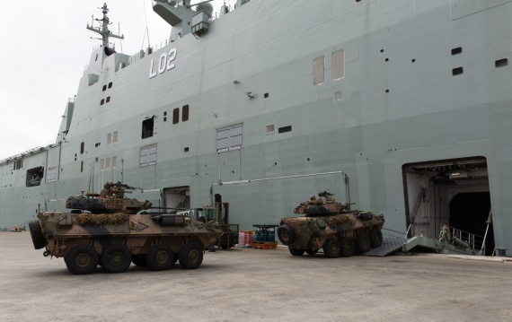 Australian Army soldiers from 2nd Cavalry Regiment drive ASLAVs (Australian Light-Armoured Vehicles) vehicles aboard HMAS Canberra in Townsville prior to a three-month deployment to Exercise RIMPAC 2016.