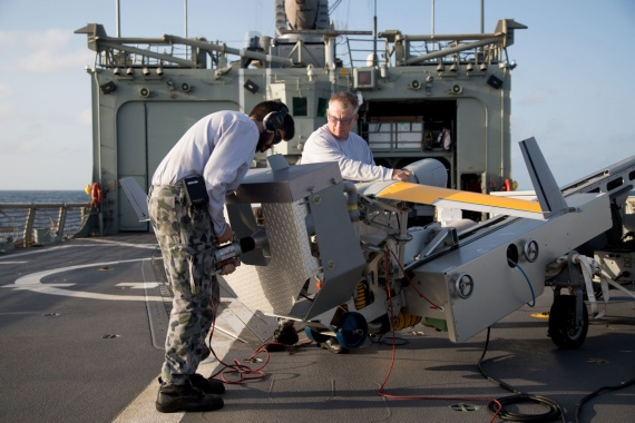 Able Seaman Aviation Technician Aircraft Daniel Debritt (left) powers up the ScanEagle propeller during unmanned aircraft vehicle (UAV) during flying stations onboard HMAS Newcastle in the Middle East region.