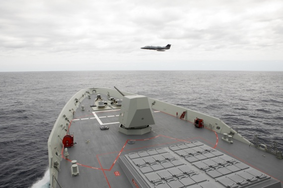 A Learjet 35 aircraft conducts a low flypast ahead of HMAS Hobart.