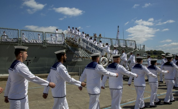 Members of the ship's company march on board during HMAS Brisbane's commissioning ceremony held at Garden Island, Sydney.