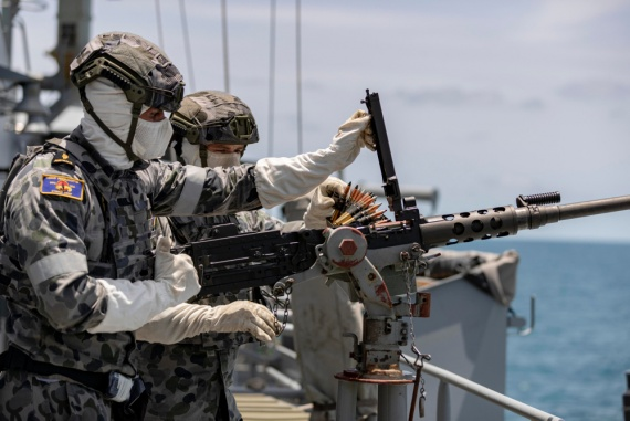 Able Seaman Boatswains Mate Matthew Thompson (left) conducts 12.7mm Browning machine gun drills on HMAS Parramatta.