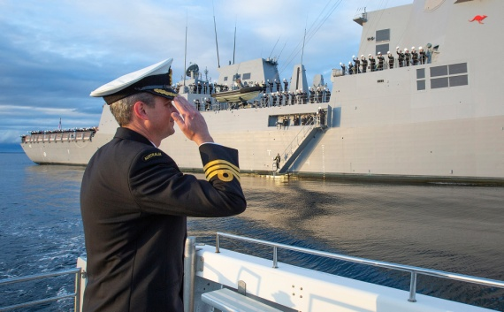 Commanding Officer HMAS Sydney, Commander Edward Seymour, RAN salutes his crew inside Jervis Bay, NSW following the ship's commissioning ceremony at sea on 18 May 2020..