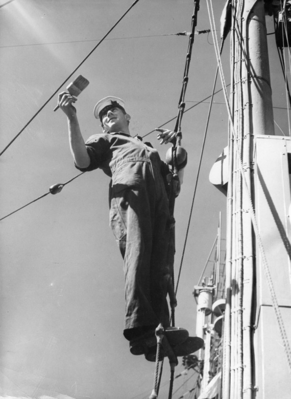 Able Seaman J.E. Olsson painting the foremast of HMAS Lithgow