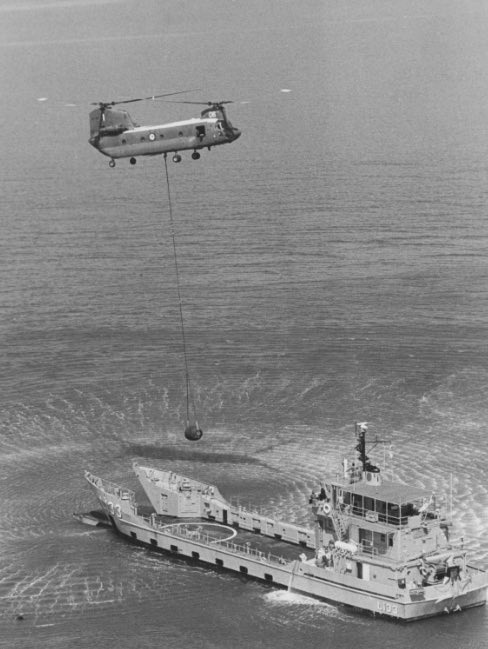 A Chinook helicopter lowering a fuel bladder on board HMAS Betano during trials in Moreton Bay.