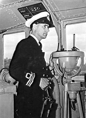 Lieutenant Commander Neville Pixley, MBE, RANR, Commanding Ofiicer of HMAS Bundaberg on the bridge of his command.