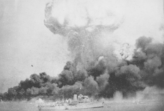 An example of the destruction wrought on Darwin – oil tanks on fire on the wharf with HMAS Deloraine visible in the harbour in the foreground. The mushroom cloud is from the explosion of the ammunition ship Neptuna.