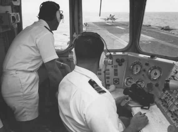 Commander Ken Douglas and Lieutenant Commander Graham Rohrsheim in Flight Control (FLYCO) watch a Skyhawk landing.