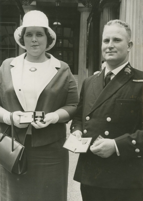 Mrs Lorraine Rogers and Chief Petty Officer Douglas Moore display the awards which were presented to them by HM the Queen on 8 July 1965. Mrs Rogers is the widow of Chief Petty Officer Johnothan Rogers who was awarded the George Cross postheumously for gallantry during the sinking of HMAS Voyager. Chief Petty Officer Moore was awarded the George Medal. (RAN Navy News 6 August 1965)