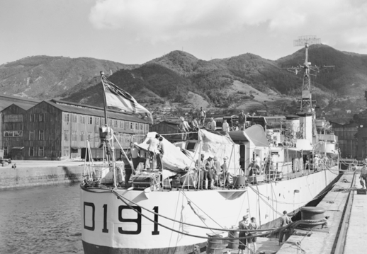 HMAS Bataan being prepared for painting at Kure by both RAN sailors and Japanese dockyard workers.