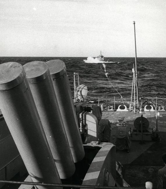 HMAS Buna after under tow from HMAS Parramatta after losing her bow door