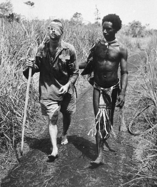 Papuan orderly Raphael Oimbari assists the wounded Private George 'Dick' Whittington at Buna on Christmas Day 1942
