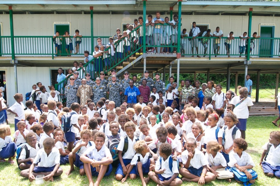Members of HMAS Labuan's ship's company with the students and teachers of McMahon Community School at Tulaghi, Solomon Islands, 16 September 2014. While in the Solomon Islands, the Landing Craft Heavy took delivery of education, medical and flood relief supplies and transported them to remote communities.