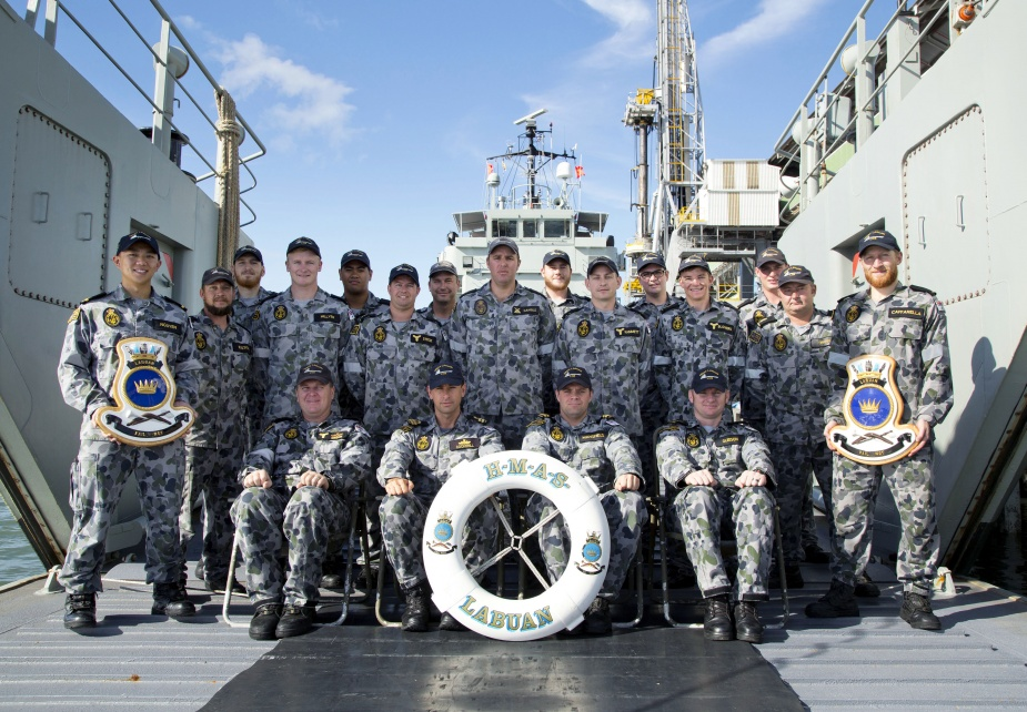 The crew of HMAS Labuan on the tank deck alongside their home port of HMAS Cairns, Queensland, 29 May 2014