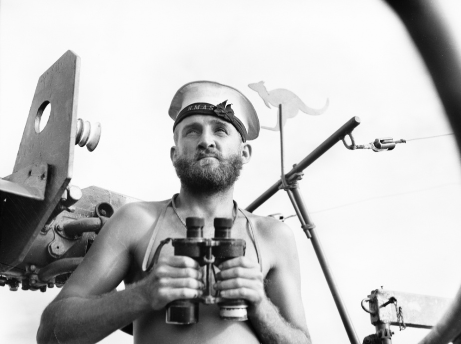 Able Seaman J Conway on watch in ML 802, Jacquinot Bay, New Guinea, 28 January 1945. Note the kangaroo cut-out attached above the gun mount. (AWM 078677)