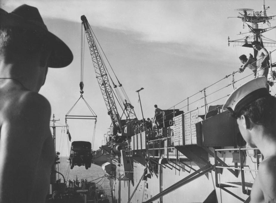 Sydney disembarking cargo onto an Army LSM at Jesselton.