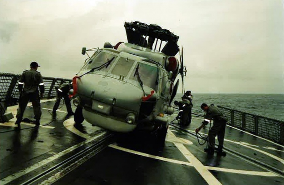 Tiger 75 being latched down to the flight deck of HMAS Melbourne after landing during a big swell, 1998. Image: Courtesy Rick Neville.