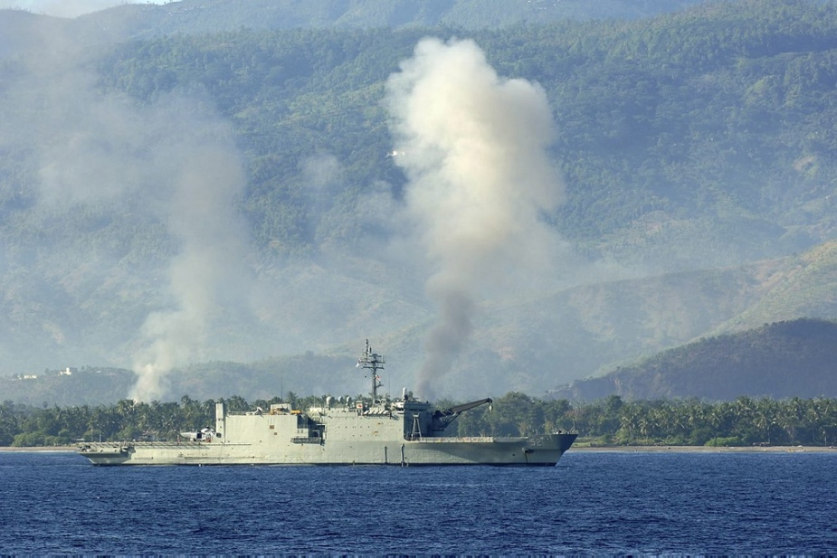 HMAS Manoora lies at anchor off the coast of Dilli, East Timor, as plumes of smoke rise into the air from the direction of the city during Operation ASTUTE.