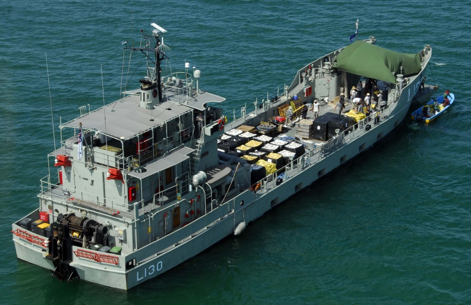 HMAS Wewak, sits off the coast at Gona Beach in Papua New Guinea, with a load of food, water and medical aid assistance to be moved out by small craft During Operation PNG Assist.