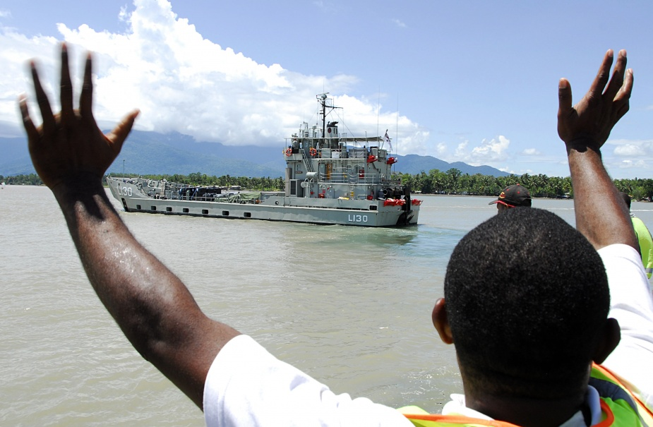 A local Papua New Guinean man who helped load aid for villages affected by floods after Cyclone Guba waves goodbye to Royal Australian Navy Landing Craft Heavy HMAS Wewak from Lae port, in Papua New Guinea during Operation PNG Assist.