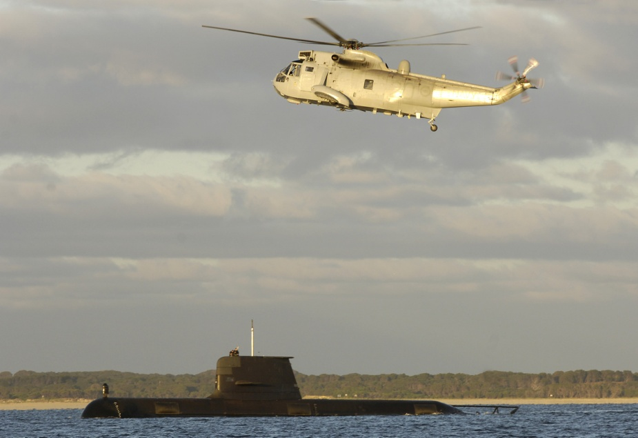A SK50 Sea King helicopter flies over HMAS Collins in December 2007.