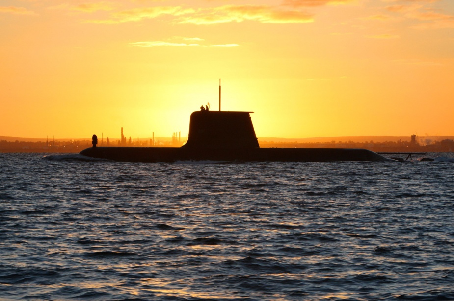 HMAS Collins sails out through the channel in Cockburn Sound at sunrise.