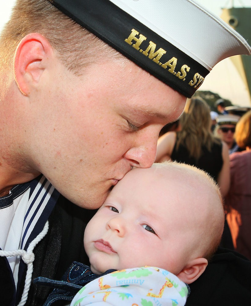 Able Seaman Mathew Avery with his 14 week old son Riley, at the welcome home ceremony for HMAS Sydney in Sydney after five months away on Northern Trident.