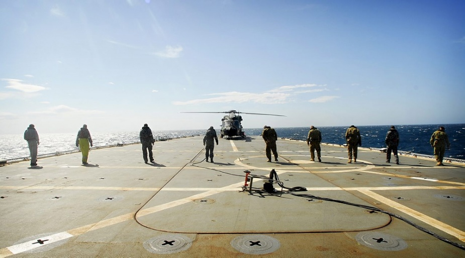 Ground crew presonnel onboard HMAS Manoora inspect the Flight Deck to ensure there are no loose foreign objects prior to commencing MRH 90 First of Class Flight Trials.