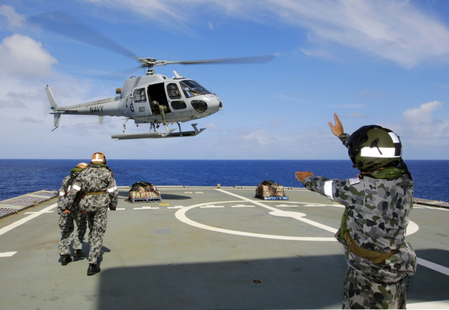 HMAS Tobruk's flight deck team is sent to attach a cargo net to Tobruk's AS350BA Squirrel helicopter (Taipan 01) while they conducted vertical replenishments from the ship to a designated drop off area ashore during Operation SAMOA ASSIST.