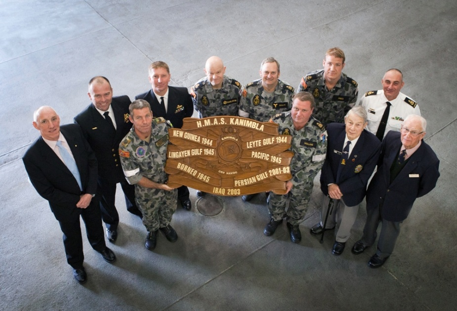 Captain Dave McCourt, RAN (Retd), Commander Timothy Byles, RAN, Commander Greg Swinden, RAN, Sten Karlsson, Glen Schultz, Lynton Price, Stephen Kypreos, Front row - SGT Andrew Bayly, Bernard Mullane, Mr Keith Bray and Mr Don Dykes former Kanimbla (I) crewmen. The battle honour board displayed in this image represents all the battle honours won by RAN ships to carry the name Kanimbla. The men in the photo were each present in at least one of the operations reflected on the board.