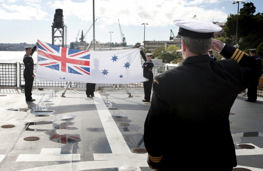 Commander Stephen Dryden, RAN Commanding Officer HMAS Manoora salutes the ships Australian White Ensign as it is formerly decommissioned on the flight deck at Fleet Base East.