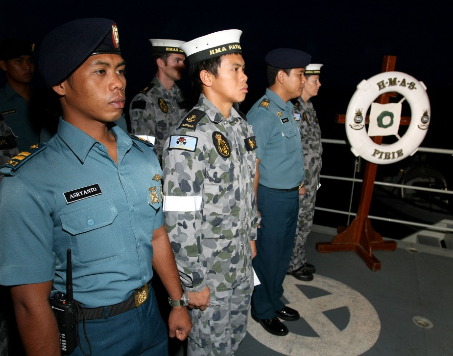 Crew members of Assail Three conduct an Anzac Day Dawn Service on the quarterdeck of Armidale Class Patrol Boat HMAS Pirie, joined by the ship's company of KRI Kakap.