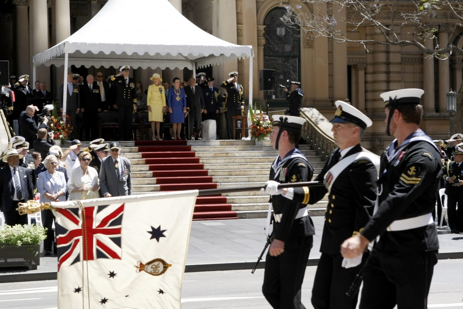 The Queens Colours marches past the reviewing officers in front of Town Hall, Her Excellency the Honourable Quentin Bryce AC, CVO Governor-General of the Commonwealth of Australia and Chief of Navy, Vice Admiral Ray Griggs AO, CSC, RAN for the Combined Navies Parade through the City of Sydney as part of the Royal Australian Navy's International Fleet Review 2013.
