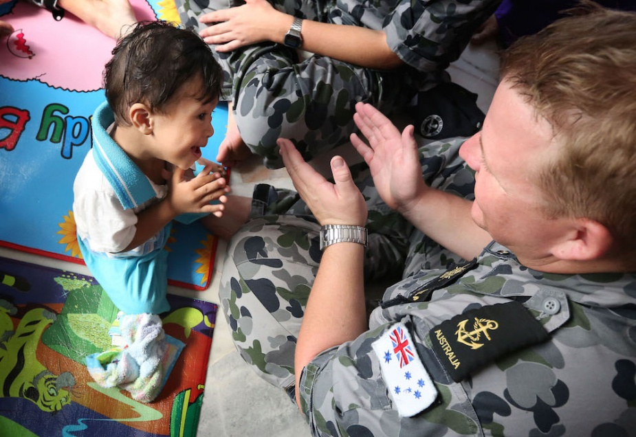 Leading Seaman Steven Head plays with one of the children at a local centre for children with special needs in Lumut, Malaysia.