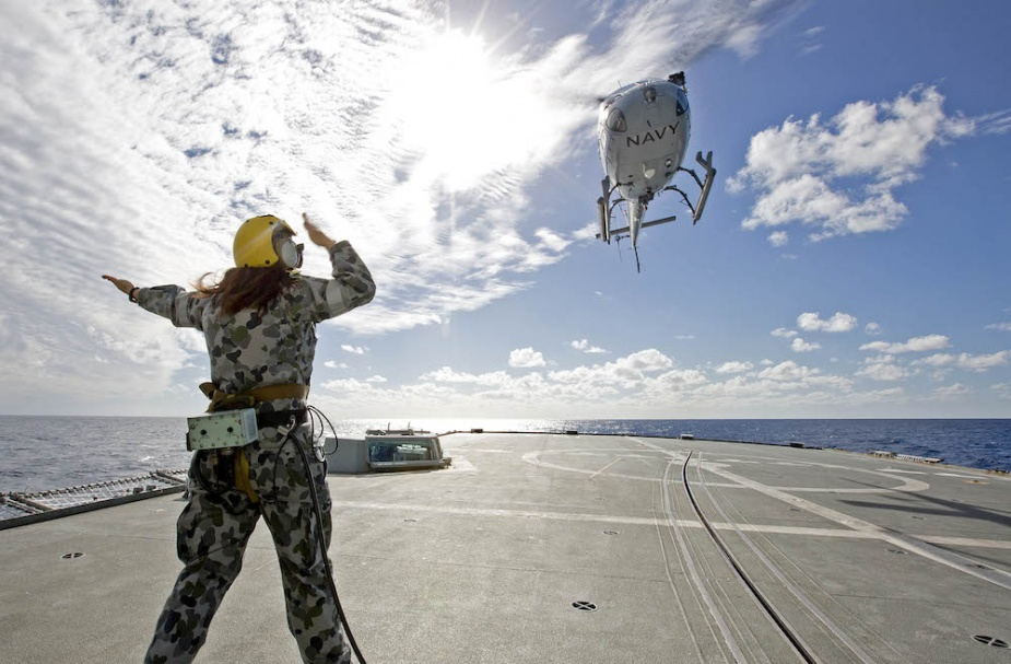 Leading Seaman Maritime Logistics - Steward Stacey Licence, directs the Squirrel Helicopter to leave the flight deck of HMAS Parramatta during training leading up to Operation Solania.