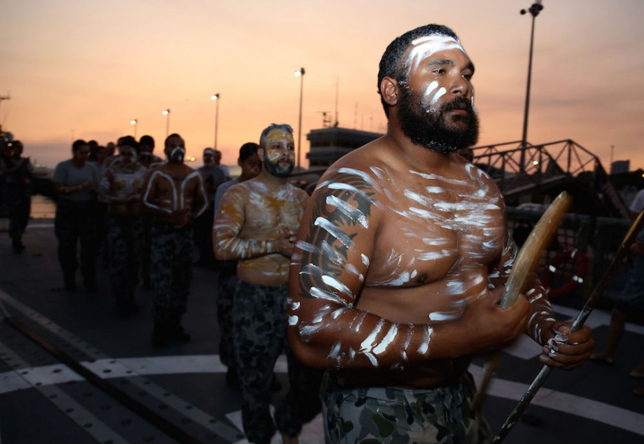 Indigenous performance troupe Bungaree performs on the flight deck of HMAS Sydney (IV) alongside Fort Hill Wharf during an Official Reception as part of Exercise KAKADU 2014 in Darwin.