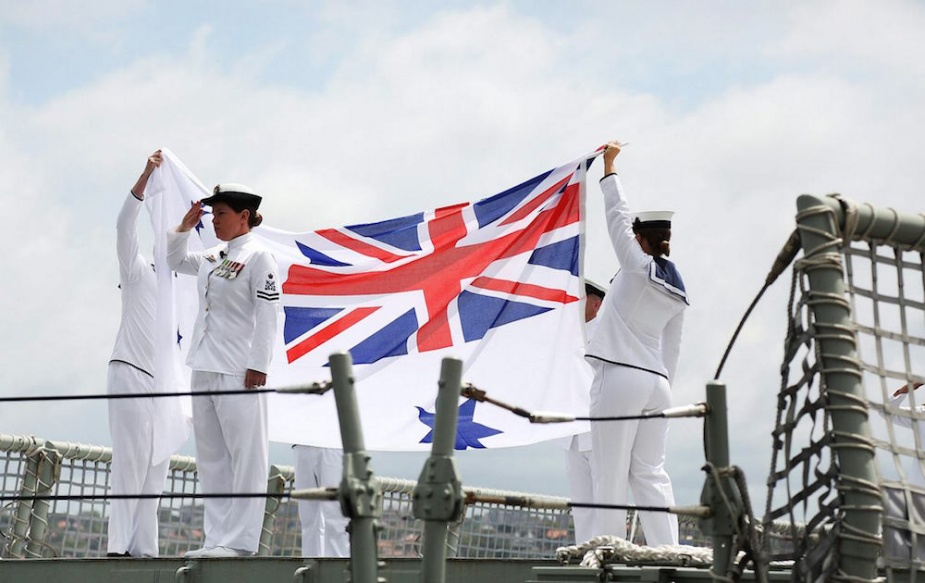 Crew members fold the Australian White Ensign on HMAS Sydney for the last time as part of the decommissioning ceremony of HMAS Sydney at Garden Island, Sydney.