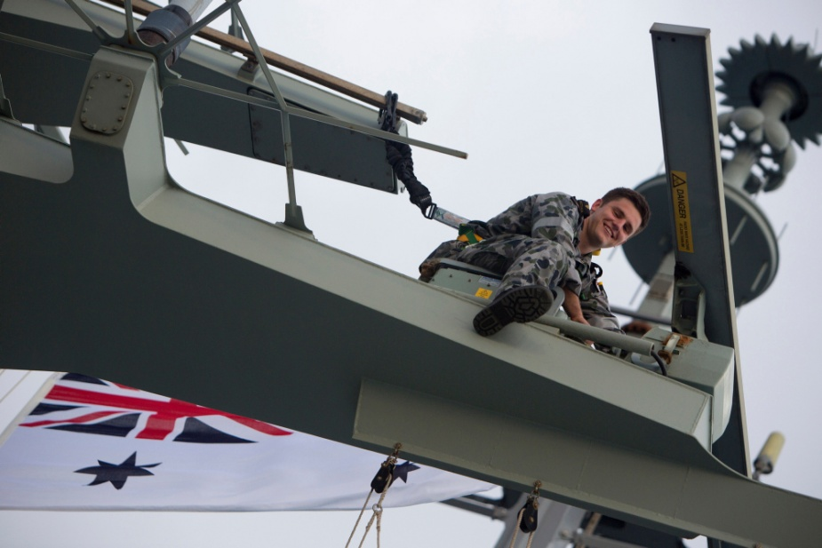 Able Seaman Electronics Technician Charles Smith-Luck sits high on the forward mast conducting maintenance on one of the ships radars. Photographer: ABIS Richard Cordell.
