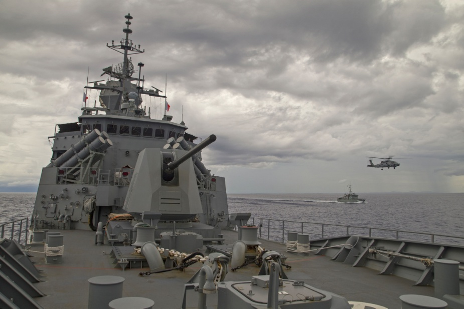 FSS Independence steams alongside HMAS Parramatta as HMAS Parramatta's embarked MH-60R Helicopter 'Warlock' flies between the two ships in the waters of Yap, Micronesia.