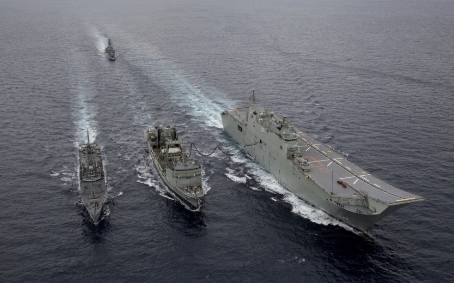 HMAS Success (centre) conducts a replenishment at sea with HMA Ships Adelaide (right) and Melbourne followed by HMAS Toowoomba.