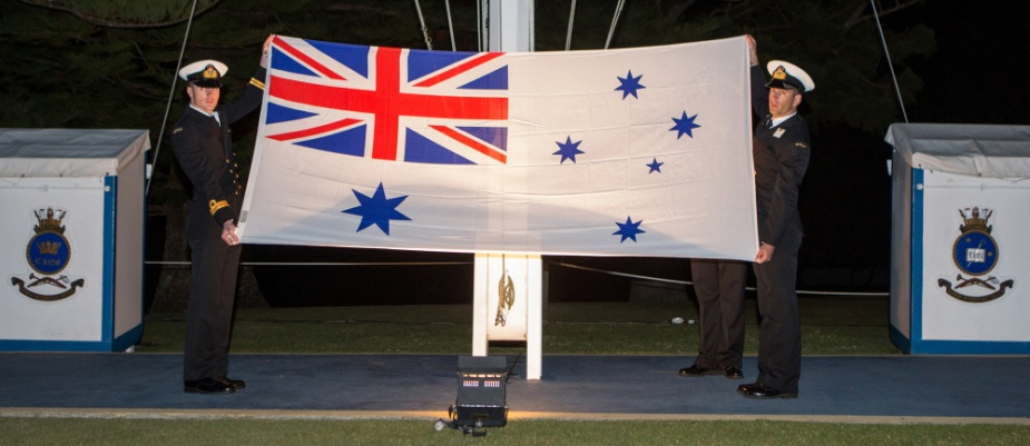 Members of the graduating class of New Entry Officers' Course 58 display the Australian White Ensign during a Ceremonial Sunset at HMAS Creswell in June 2018.