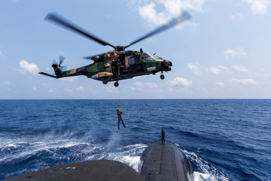 A Royal Australian Navy sailor is lowered to the casing of HMAS Collins from an MRH-90 Maritime Support Helicopter while sailing in the Bay of Bengal during AUSINDEX 2019.
