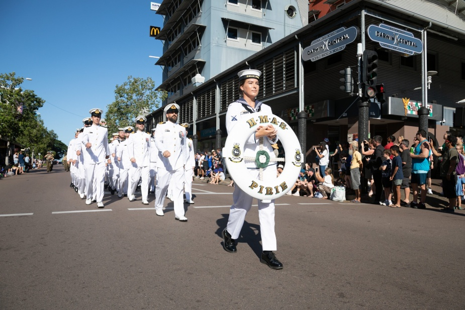 Seaman Boatswains Mate Karin Smit bears the ceremonial life ring for HMAS Pirie as the ship's company marches through the streets of Darwin on Anzac Day 2019.
